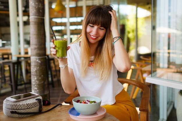 Sorglose lächelnde frau, die gesundes veganes frühstück isst.