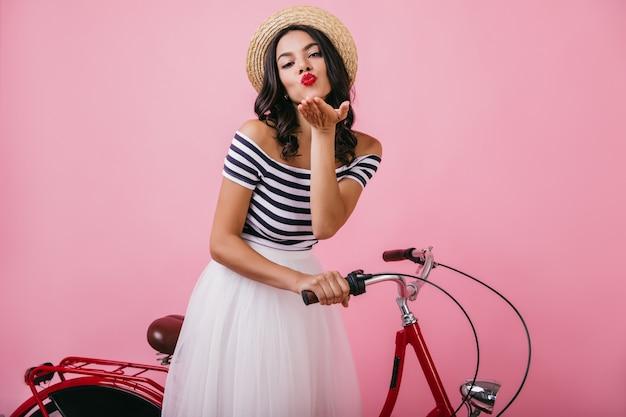 Sorglose lateinamerikanische frau mit eleganter frisur, die luftkuss sendet. innenfoto des niedlichen gegerbten mädchens, das neben rotem fahrrad aufwirft.