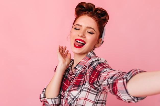 Sorglose pinup-dame, die selfie nimmt. studioaufnahme des kaukasischen ingwermädchens im karierten hemd, das auf rosa raum aufwirft.