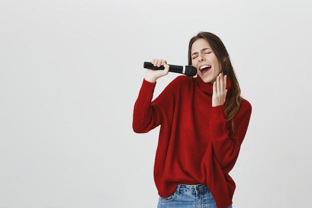 Sorglose süße frau, die karaoke im mikrofon singt