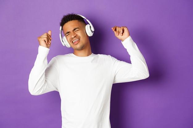 Sorgloser afroamerikaner tanzt, hört musik in drahtlosen kopfhörern