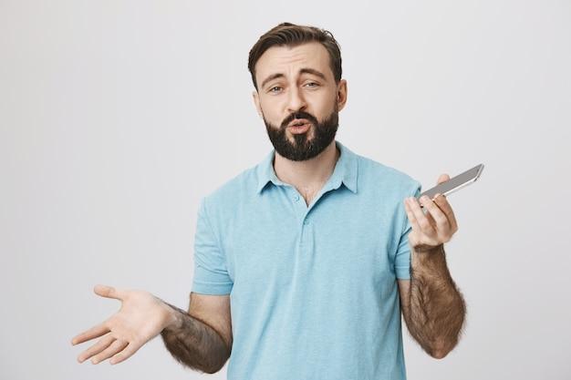 Sorgloser bärtiger erwachsener mann, der handy benutzt und spricht