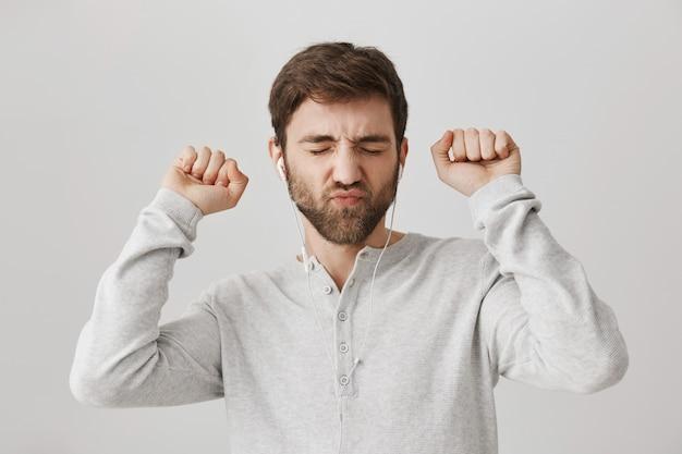 Sorgloser dummer bärtiger kerl, der musik in den kopfhörern hört und tanzt