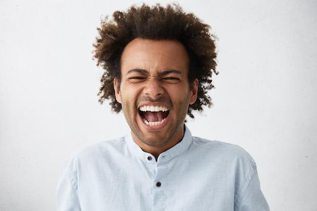 Sorgloser freudiger gutaussehender afroamerikanischer mann mit buschiger frisur