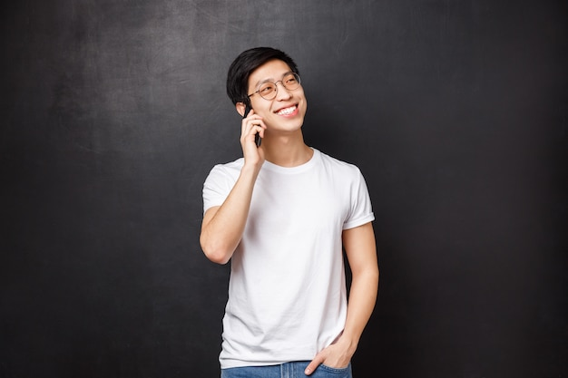 Sorgloser fröhlicher asiatischer mann, der mit freundlicher haltung am telefon spricht