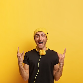 Sorgloser fröhlicher kerl macht rock'n'roll-geste, bringt positive stimmung, hört rockmusik in kopfhörern