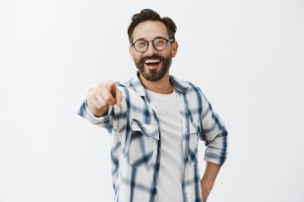 Sorgloser glücklicher bärtiger reifer mann, der aufwirft
