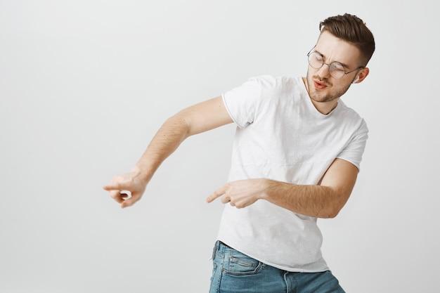 Sorgloser glücklicher mann, der nach links zeigt, während er in drahtlosen kopfhörern tanzt und musik hört