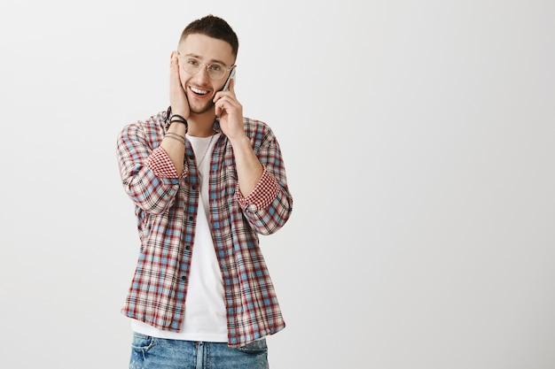 Sorgloser junger mann, der mit seinem telefon aufwirft
