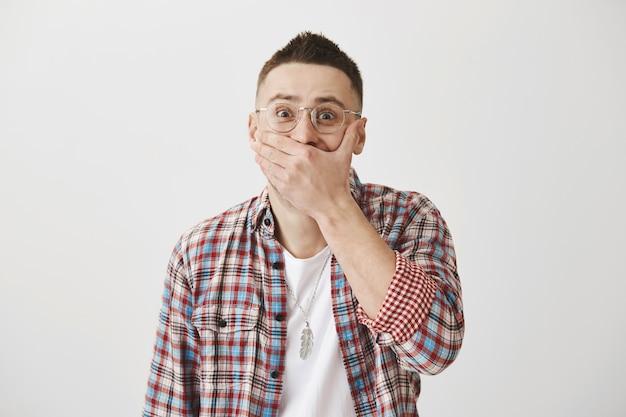 Sorgloser junger mann mit brille posiert