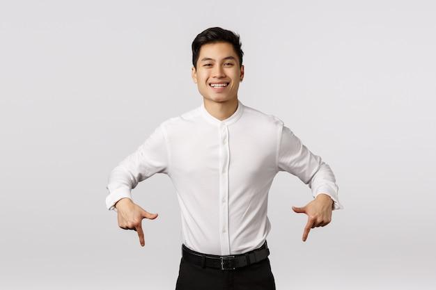 Sorgloser, lächelnder netter und froher asiatischer tausendjähriger kerl in der formellen kleidung, im hemd und in den hosen, unten zeigend