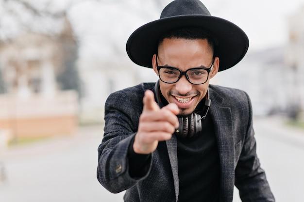 Sorgloser mann, der finger mit schlauem lächeln zeigt. außenporträt des raffinierten afrikanischen männlichen modells lokalisiert