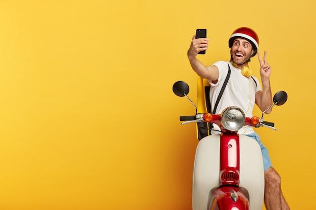Sorgloser positiver gutaussehender männlicher fahrer auf roller mit rotem helm