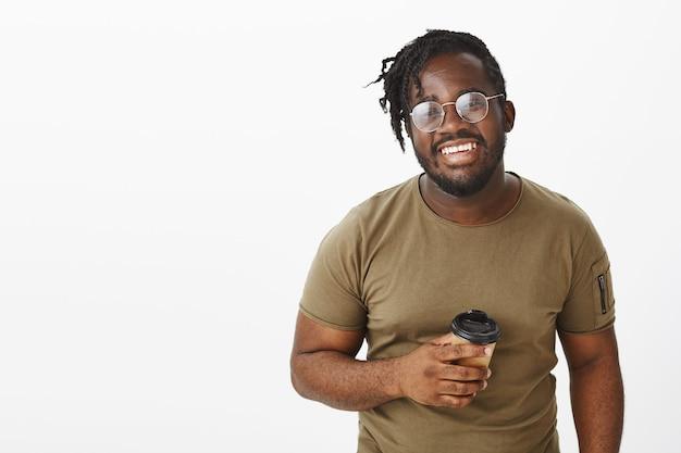 Sorgloser typ mit brille posiert mit seinem kaffee an der weißen wand