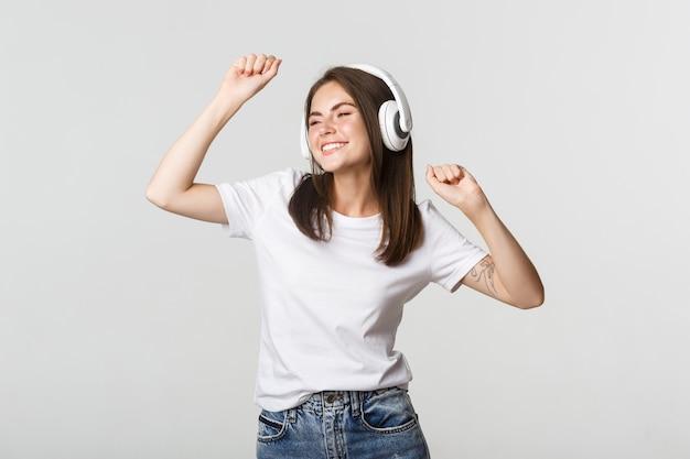 Sorgloses attraktives mädchen tanzt und hört musik in drahtlosen kopfhörern.