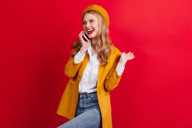 Sorgloses blondes mädchen, das am telefon spricht und tanzt. modische französische frau in baskenmütze, die smartphone an der roten wand hält.