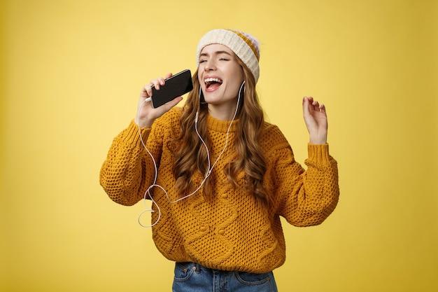 Sorgloses charmantes mädchen mag karaoke und hat spaß beim hören von lieblingsliedern, die kabelgebundene kopfhörer tragen, smartphone-mikrofon halten, laut singen und tanzen genießen, zeit alleine verbringen