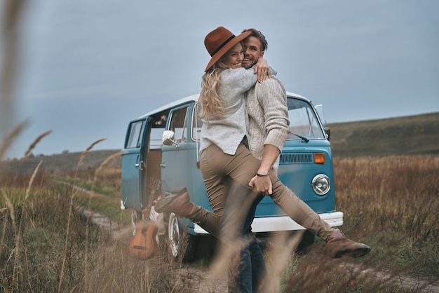 Sorgloses glück. schönes junges paar, das umarmt und lächelt, während es nahe dem blauen retro-stil-minivan steht