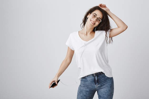 Sorgloses glückliches mädchen, das zur musik in den kopfhörern tanzt, mit handy