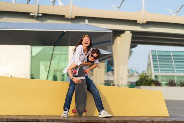 Sorgloses junges paar hat spaß freundin huckepack freund liebhaber mädchen und kerl skateboarder