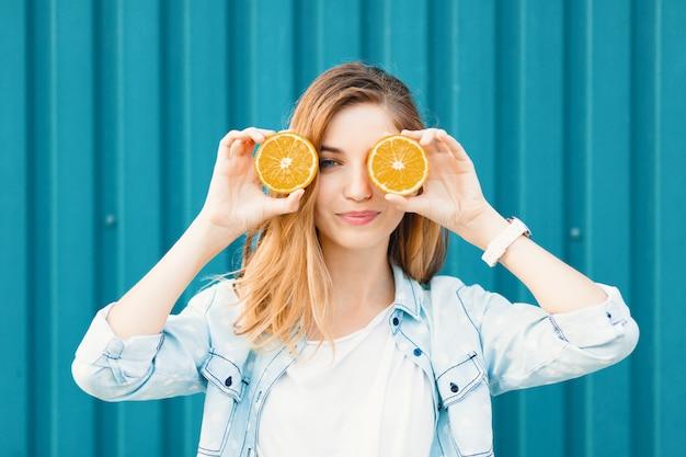 Sorgloses junges schönes mädchen, das stattdessen zwei halfs auf orangen verwendet