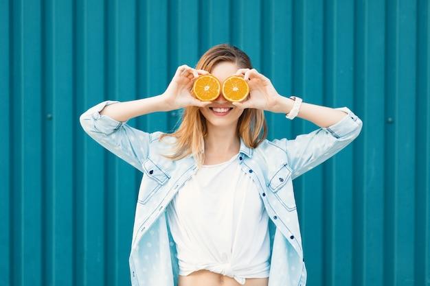 Sorgloses junges schönes mädchen, das zwei halfs auf orangen anstelle der gläser über ihren augen verwendet