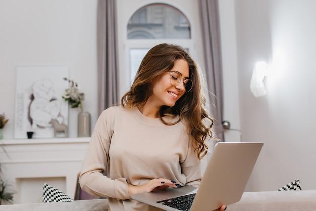 Sorgloses kluges mädchen im beige hemd, das mit romantischem lächeln aufwirft, arbeitet mit computer
