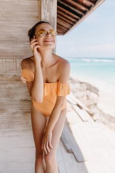 Sorgloses mädchen, das am strand mit geschlossenen augen und aufrichtigem lächeln aufwirft. außenaufnahme der prächtigen schlanken dame im orangefarbenen badeanzug.