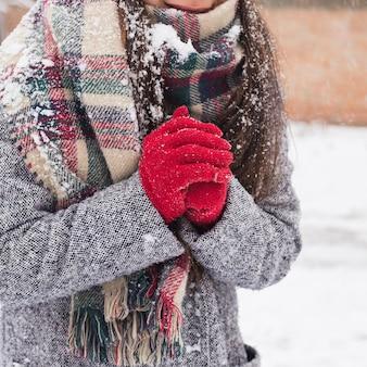 Sorgloses mädchen, das an einem wintertag lacht. außenfoto der jungen europäischen frau, die an einem verschneiten morgen nahe dem haus betrügt.