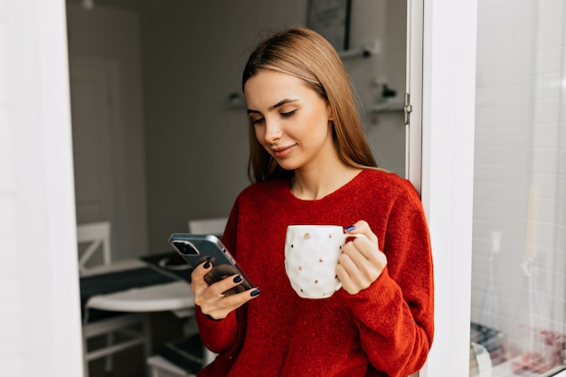 Sorgloses mädchen, das tee auf balkon trinkt und smartphone benutzt. foto der angenehmen frau im gestrickten roten pullover, der kaffee genießt.