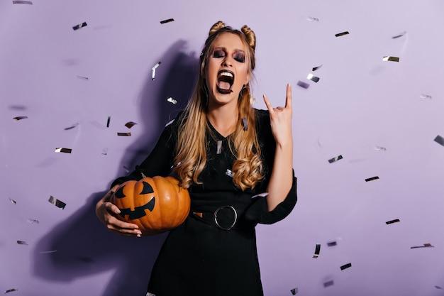 Sorgloses mädchen im halloween-kostüm, das für partei vorbereitet. nette hexe mit kürbis, der unter konfetti steht.