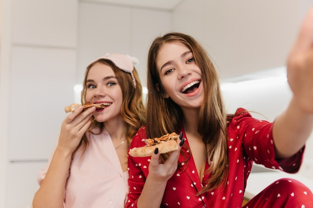Sorgloses mädchen trägt einen roten nachtanzug, der morgens selfie macht und lacht. charmante blonde frau, die pizza mit vergnügen isst.