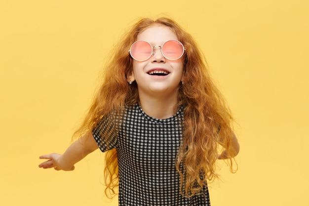 Sorgloses modisches kleines mädchen mit den gelockten roten haaren