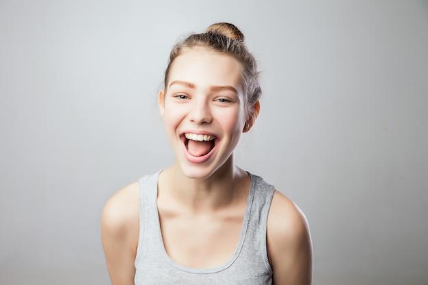 Sorgloses porträt einer lachenden und lustigen frau. echte person auf grauem hintergrund