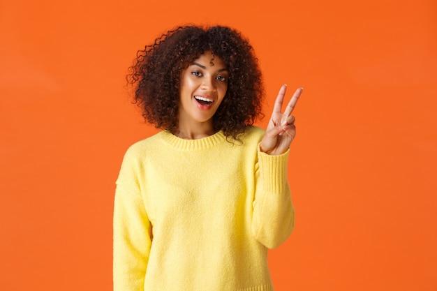 Sorgloses reizendes, dummes afroamerikanermädchen, das für foto über orange mit lächeln aufwirft und das friedenszeichen zeigt, das den käse sagt, der fröhlich und optimistisch sich fühlt, drücken positive gefühle aus