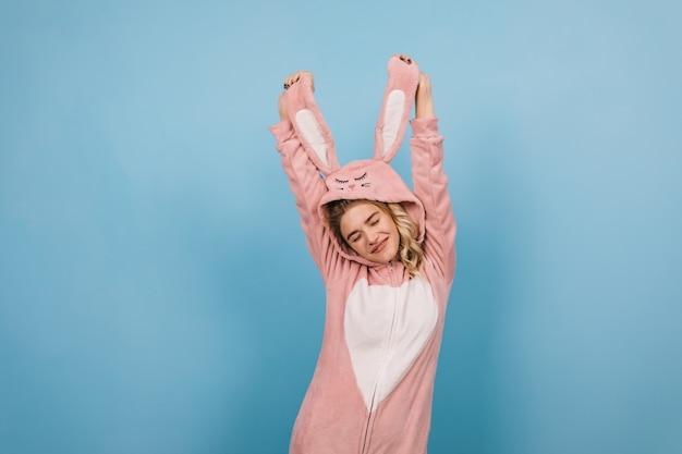 Sorgloses weibliches modell, das in rosa kigurumi tanzt