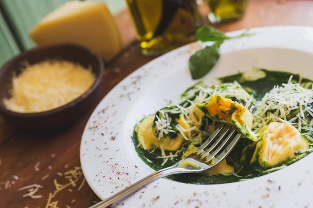 Sorrentino mit parmesankäseparmesankäse und olivenöl auf einem holztisch