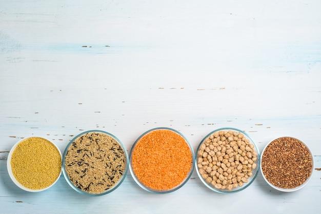 Sorten von natürlichem bio-saatgut in runden tellern aus reis, hirse, linsen, buchweizen, erdnüssen, haferflocken. der blick von oben.