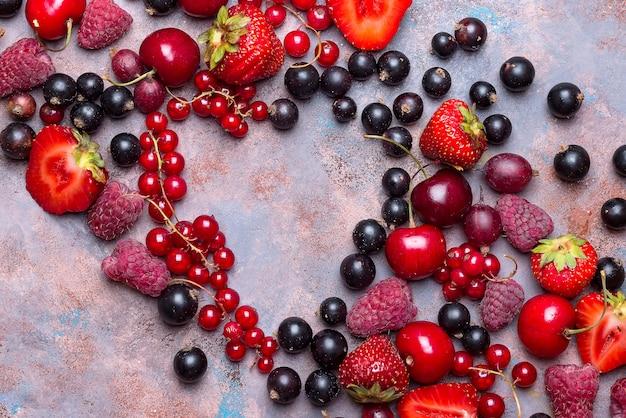 Sortierte beerenfrüchte der herzform auf steinhintergrund. flach legen