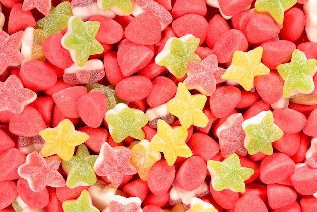 Sortierte bunte gummiartige bonbons und lutscher auf rotem hintergrund. ansicht von oben. gelee süßigkeiten.