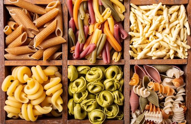 Sortierte bunte italienische teigwaren in der holzkiste