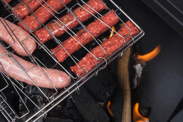 Sortierte fleischwürste auf loderndem grill