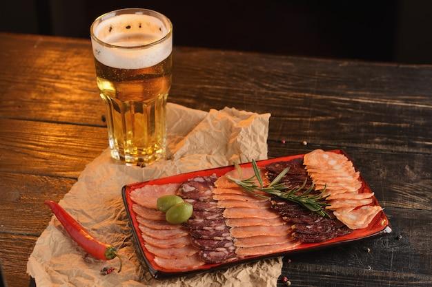 Sortierte geschnittene würste auf einer roten platte. mit einem glas bier. auf einem holztisch