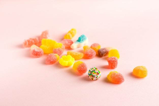 Sortierte gummiartige süßigkeiten auf rosa oberfläche