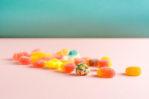 Sortierte gummiartige süßigkeiten auf rosa und blauer oberfläche