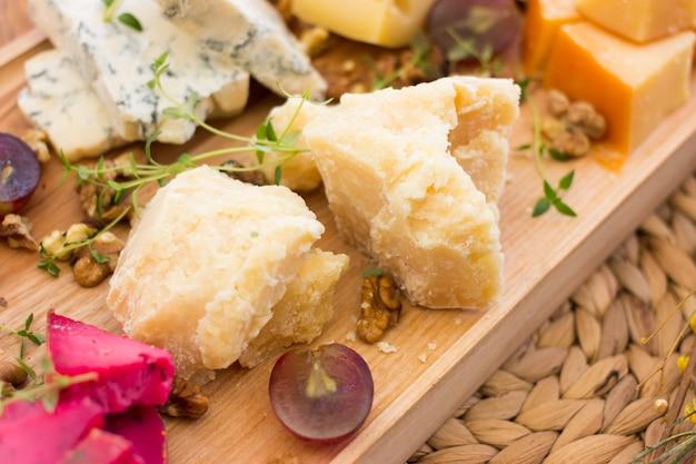 Sortierte käse mit beeren, nüssen und grüns auf einem hölzernen behälter