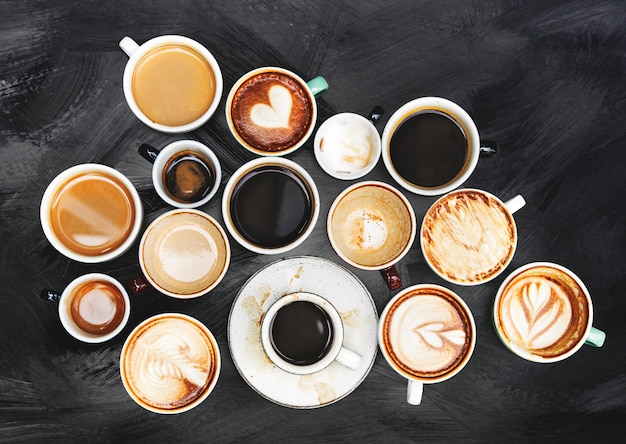 Sortierte kaffeetassen auf einem strukturierten hintergrund