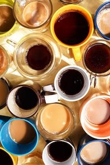 Sortierte kaffeetassen mit kaffee und auf einer tabelle. ansicht von oben.