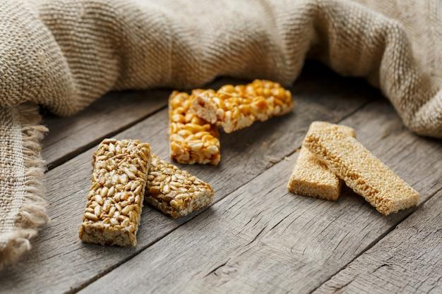 Sortierte kozinaki ,, mit sackleinen. landhausstil. leckere süßigkeiten aus den samen von sonnenblumen, sesam und erdnüssen, mit glänzender glasur überzogen.