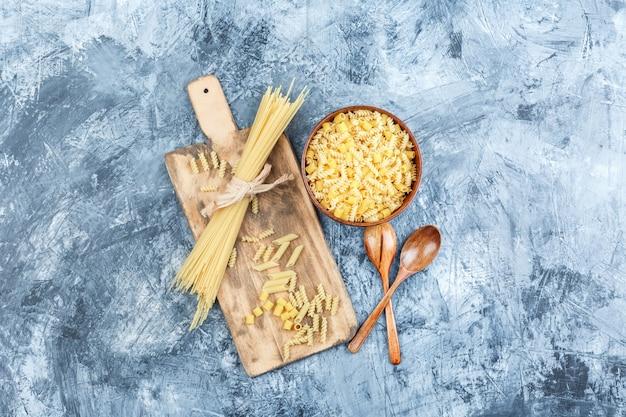 Sortierte nudeln der draufsicht in der schüssel mit holzlöffeln auf grauem gips und schneidebretthintergrund. horizontal